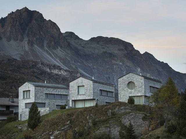 Drei moderne Häuser voer einer schriffen Felswand.