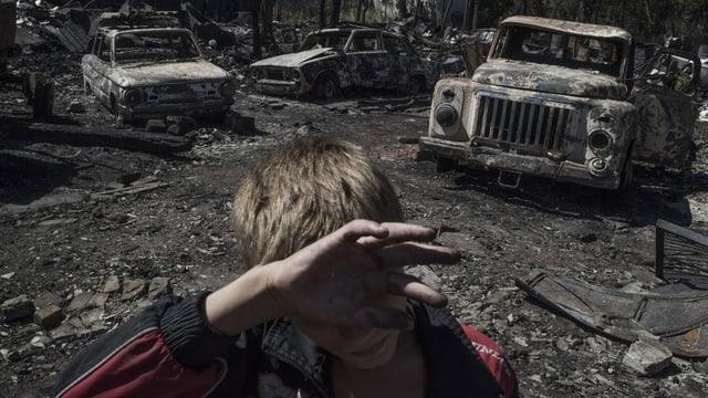 Ein Junge steht vor einem ausgebombten Auto.