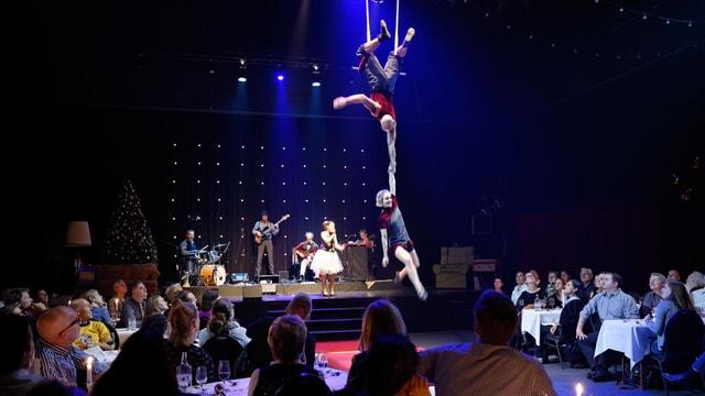 Akrobaten an einem Trapez, daneben Personen an Tischen, im Hintergrund eine Band.