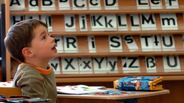 Bub vor Pult und Buchstaben
