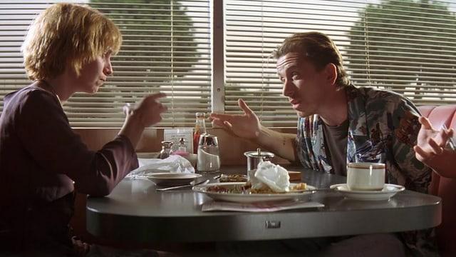 Links sitzt eine blonde Frau im Restaurant einem dunkelhaarigen Mann gegenüber. Sie diskutieren.