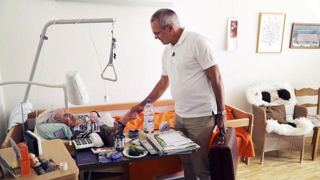 Dr. Thomas Kissling reicht einer bettlägerigen Patientin die Hand.