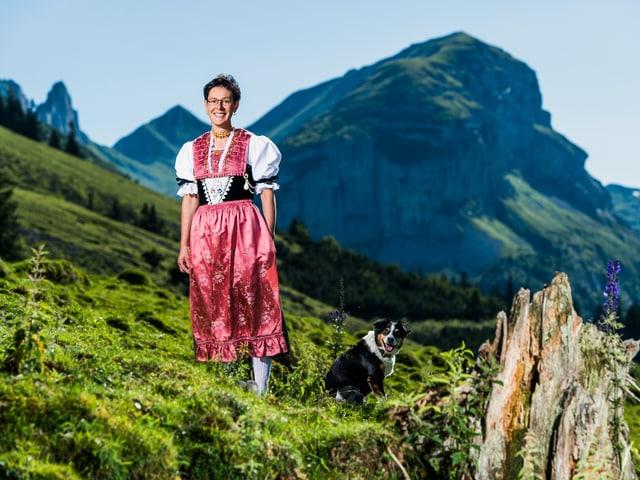 Theresia Hollenstein steht mit ihrer Tracht auf einer Bergwiese mit dem Hofhund daneben.