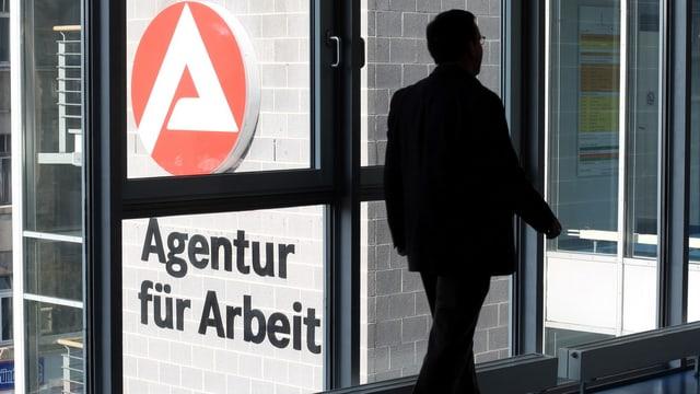 """Mann im Gegenlicht in einem Bürogebäude, auf einer Aussenmauer steht:  """"Agentur für Arbeit"""""""