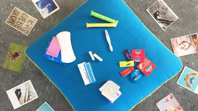 Auf einem kissen liegen Kondome, ein Schwangerschaftstest, Binden, Tampons und Pillen.