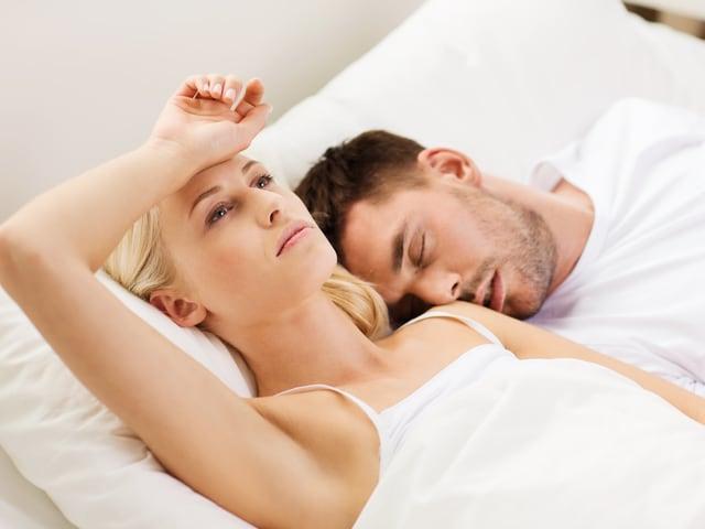 Ein Paar liegt in einem Bett. Die Frau ist wach und der Mann schläft.
