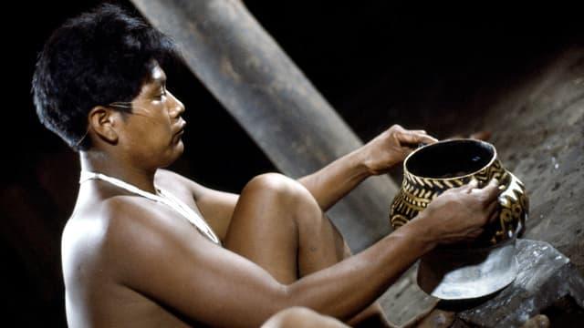 Ein Mann sitzt vor einem Tongefäss, das zur Hälfte mit gold-schwarzem Muster bemalt ist.
