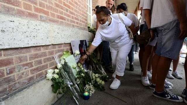 Eine Frau legt Blumen vor deinem Bild des verstorbenen Busfahrers nieder.