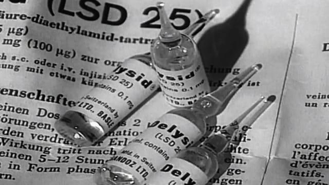 Ein mit Schreibmaschine beschriebenes Blatt mit chemischen Informationen. Darauf sind Ampullen aus einem Chemielabor zu sehen.