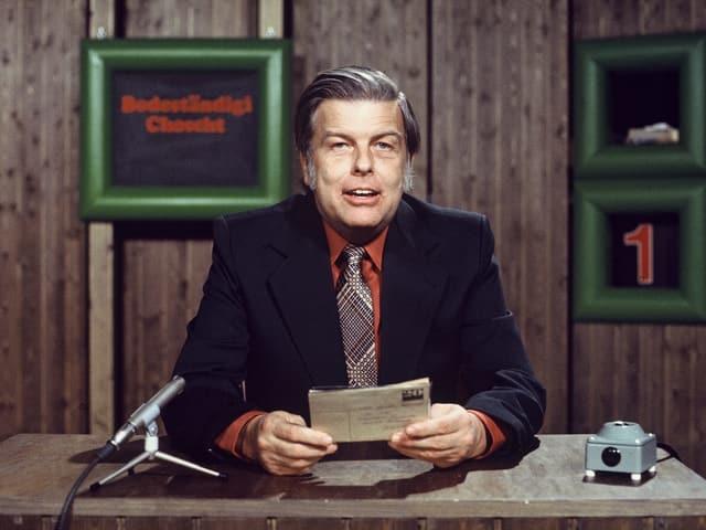 Ein Mann vor einem Mikrofon in einem Fernsehstudio.