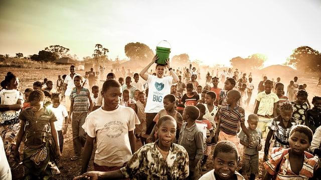 Rapper Knackeboul mit einem Eimer auf dem Kopf inmitten afrikanischer Kinder.