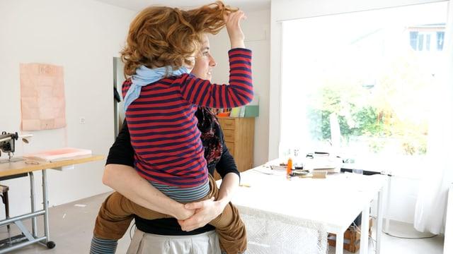Eine Frau trägt ein Kind auf dem Arm, das an seinen Haaren zieht.