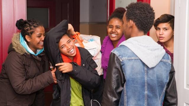 Fünf dunkelhäutige Jugendliche blödeln und lachen miteinander