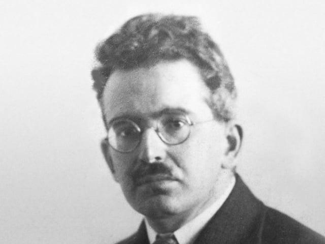 Krauses Haar, runde Brille, strenger Blick: Walter Benjamin auf einer Schwarzweissaufnahme um 1928.