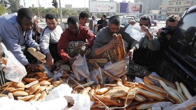 Menschen fischen Brotlaibe aus einem grossen Korb.