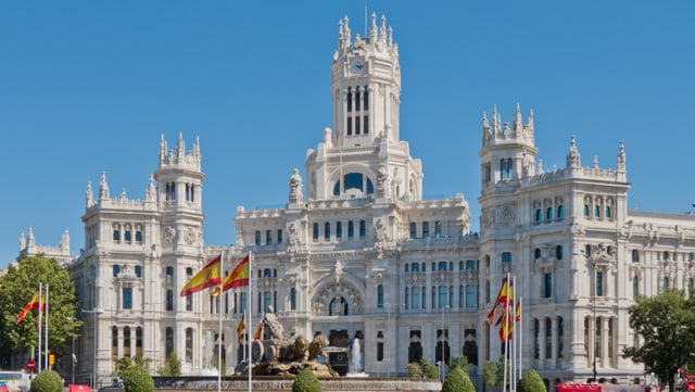 Ein weisser Palast. Im Vordergrund wehen spansiche Flaggen.