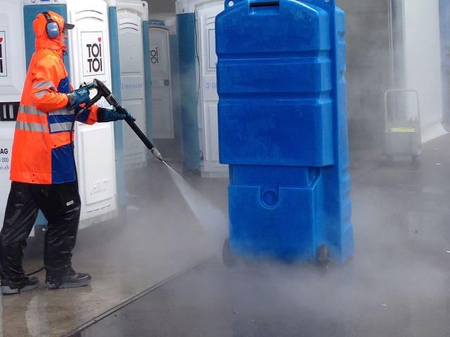 Servicemitarbeiter spritzt das WC von vorne und von hinten.