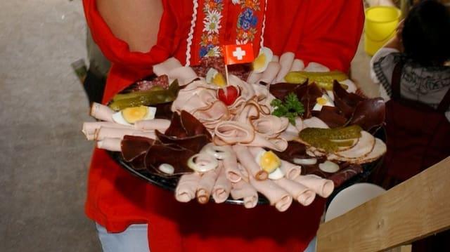 Fleischplatte mit Schweizer-Fähnchen dekoriert vor Edelweiss-Bluse.