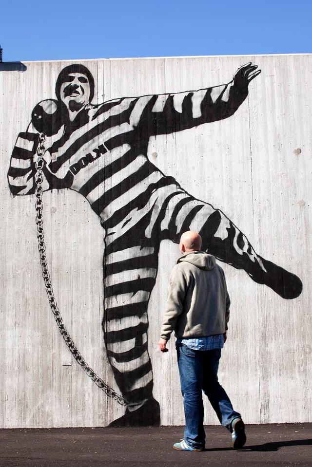 Häftling macht Kugelstossen mit seiner Fussfessel und deren Gewicht - als Bild an einer Betonwand.