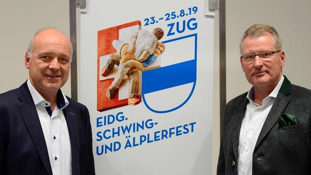 Thomas Huwyler und Heinz Tännler stehen vor dem Logo.