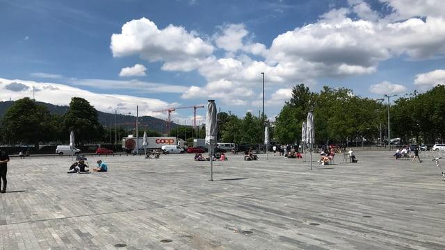 Ein grosser Platz mit Valser-Quarzit-Platten. Darauf neue weisse Sonnenschirme. Am Himmel sind weisse Wolken.
