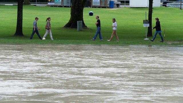 Platschvolles Aare-Flussbecken, am Ufer spatzieren Leute.
