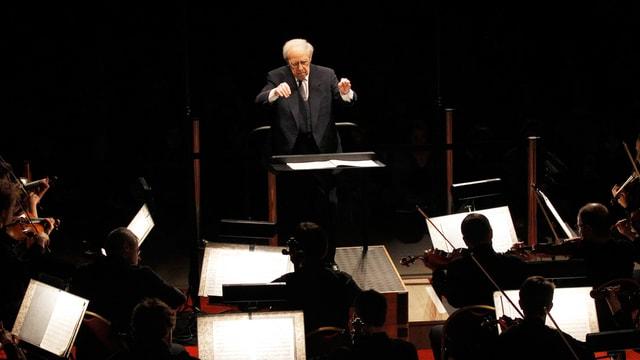 Mann dirigiert Orchester.