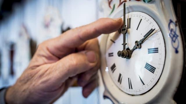 Jemand stellt die Uhr um.