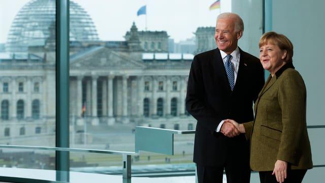 Bundeskanzlerin Angela Merkel (rechts) schüttelt die Hand von US-Vizepräsident Joe Biden im Kanzleramt. Im Hintergrund ist der Reichstag zu sehen.