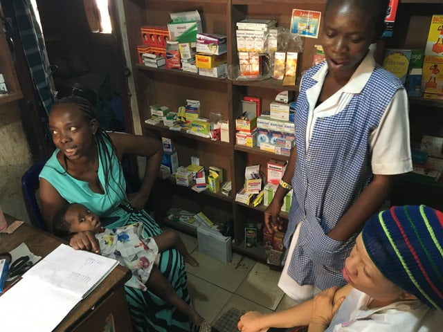 Drei Afrikanerinnen, ein hält ein Baby vor einem Gestell mit Medikamenten.