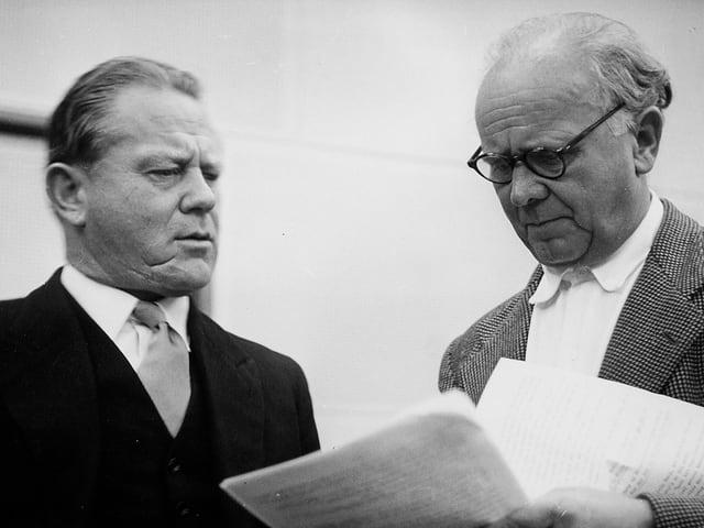 Zwei Männer mit Manuskripten.