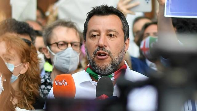 Salvini spricht in Mikrfone und Kameras inmitten einer Menschenmenge, die Maske hat er unter dem Kinn.