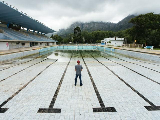 Ein Mann steht in einem leeren Pool.