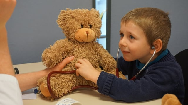 Kind prüft den Herzschlag eines Teddybärs.