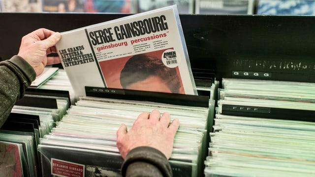 Eine Kiste mit Schallplatten in einem Laden. Jemand zieht ein Album von Serge Gauinsbourg heraus.