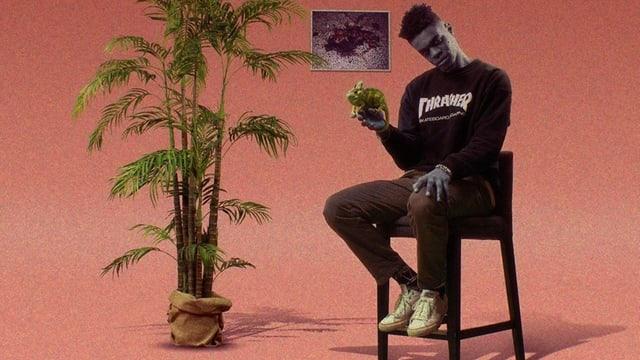 Ein schwarzer Mann sitzt auf einem Barstuhl und hält eine Ananas