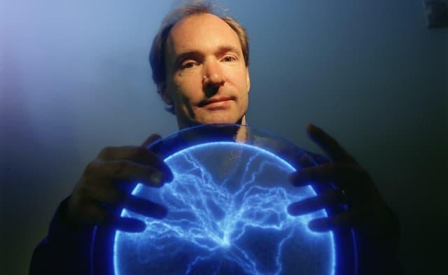 Ein Mann hält eine Art Leuchtkugel in den Händen.