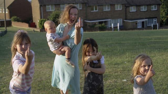 Eine Frau und drei Kinder zeigen den Mittelfinger.