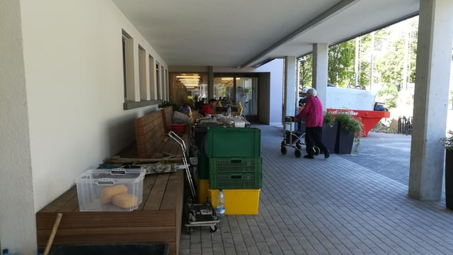 Frau mit Rollator, verschiedene Gegenstände vor Gebäude.