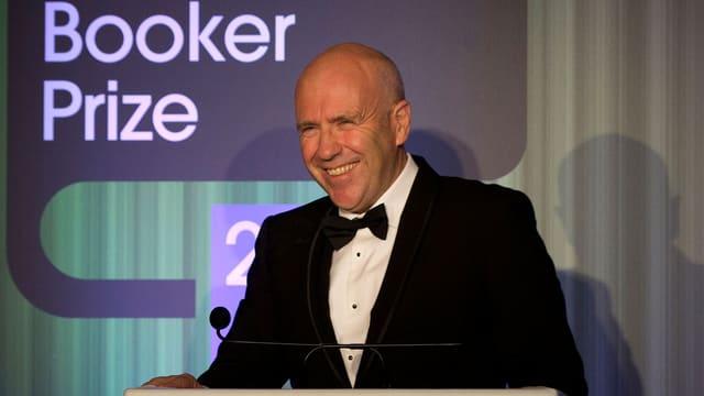 Richard Flanagan, im Smoking, steht lachend an einem Rednerpult.