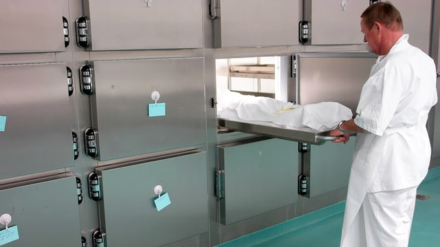 Blick in eine Pathologieabteilung, wo ein Mann in weisser Kleidung eine Trage in einen Kühlraum schiebt.