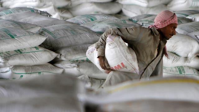 Ein indischer Arbeiter trägt einen Zementsack.