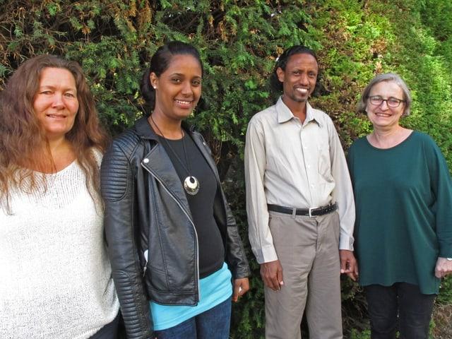 Vier Menschen stehen vor einem grünen Busch.