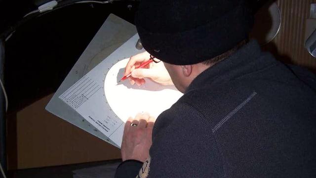 Ein Mann skizziert mit Bleistift auf einem Papier.