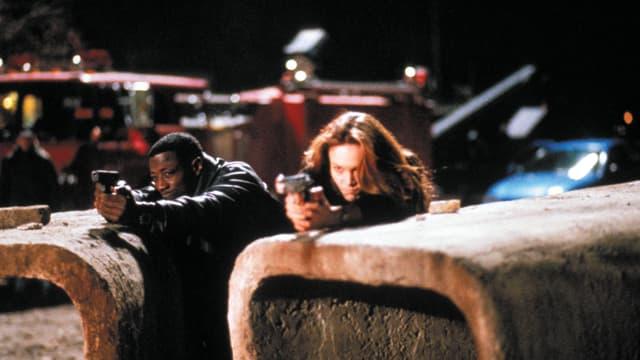 Ein Polizist und eine Agentin gehen in Deckung und zielen mit der Waffe auf ein unbekanntes Ziel.