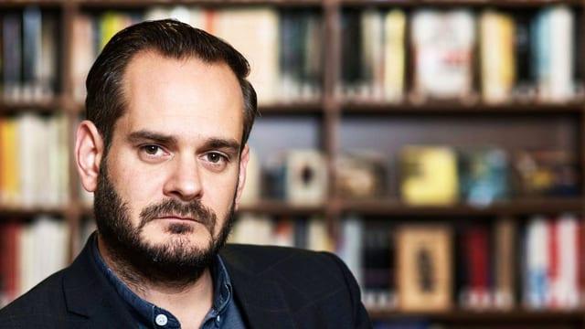 Jonas Lüscher sitzt vor Büchern..