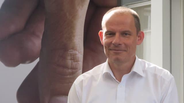 Finanzchef Bruno Edelmann steht vor einem Tornos-Plakat