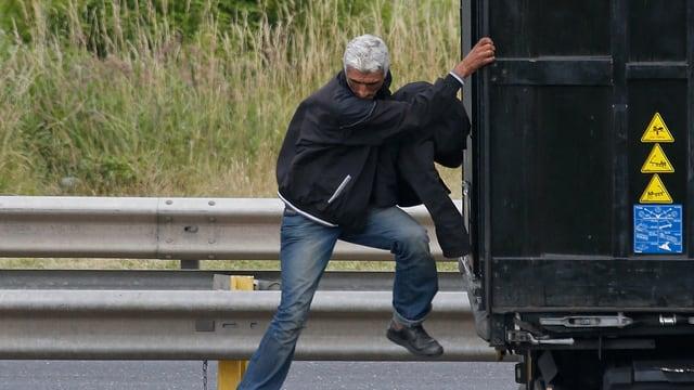 Flüchtling versucht im französischen Calais auf einen Lastwagen zu klettern.