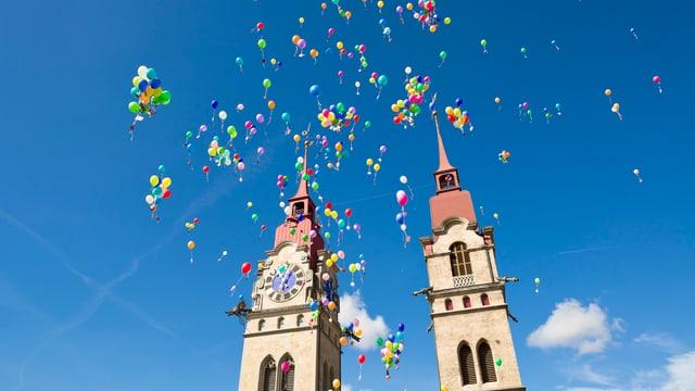 Bunte Ballone steigen vor Kirchtürmen in Winterthur in den Himmel