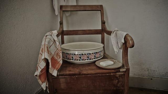 Schüssel, Stück Seife, Tüechli auf einem Holzstuhl